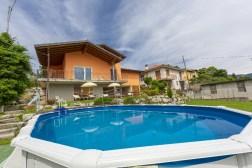 Het bovengrondse zwembad in de grote tuin met op de achtergrond het terras en de villa