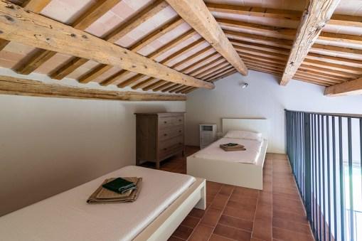 Slaapkamer 2 met twee 1-persoonsbedden op de open vide