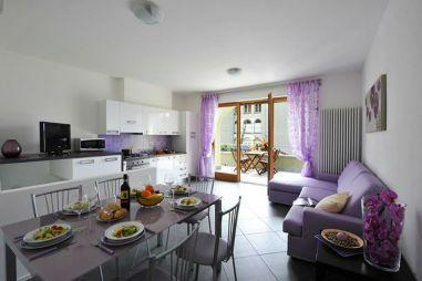 Woonkamer met volledig uitgeruste open keuken en openslaande deuren naar het terras