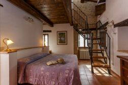 Vakantiehuis Noce | Slaapkamer met 2-persoonsbed en trap naar de vide met de derde slaapkamer