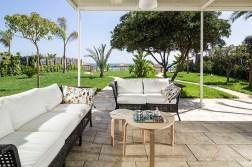 Prive-terras met loungeset aan de voorkant grenzend aan de tuin en met uitzicht op zee