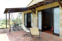 Overdekt prive-terras met een tafel, stoelen en ligstoelen
