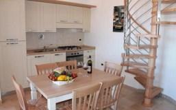 Woonkamer met open keuken en trap naar de vide