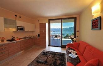 Woonkamer met open keuken en toegang tot het terras