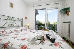 Slaapkamer 1 met 2-persoonsbed en balkon
