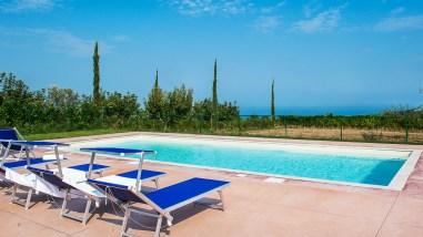 Het omheinde prive-zwembad met uitzicht op zee