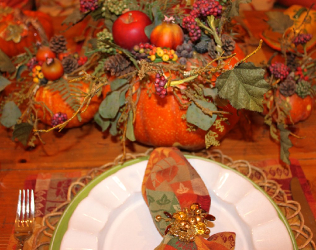 Pumpkin with autumn fruit and foliage-themed focal point of the tablescape.