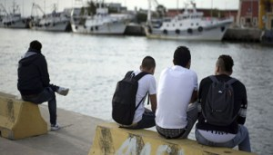 In this photo taken on Thursday, April 21, 2016, unaccompanied minors from Egypt, from left, 16-year-old Fathi, 17-year-old Saied, 17-year-old Gamal, and 17-year-old Ayman, last names not available, sit next to the river Tiber after an interview with The Associated Press, in Fiumicino, 30 kilometers (19 miles) west of Rome. All across Europe, there is a growing shadow population of thousands of under-age migrants who are living on their own, without families. They hide silently and in plain sight, rarely noticed in the crowd. Nobody even knows how many of them there are -- Europol estimates broadly that at least 10,000 kids have gone missing from shelters or reception centers.(AP Photo/Andrew Medichini)