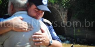 Pai da vítima é confortado por GCM. Ao fundo, agente da Defesa Civil tenta localizar corpo de adolescente