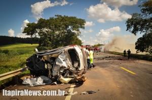 Carro ficou irreconhecível; ao fundo o caminhão em chamas