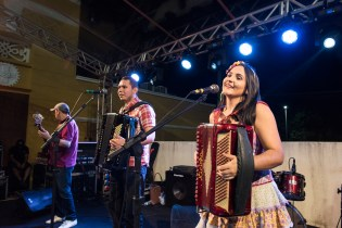 Man playing guitar, man and woman each playing accordions on stage in Fortaleza, Brazil