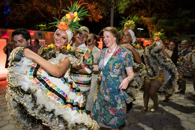 Redhaired woman in blue floral dress in dancing procession with traditional Brazilian dancers