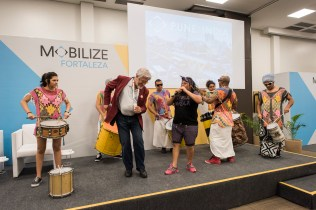 Man in red blazer dancing along with drummers at event in Brazil