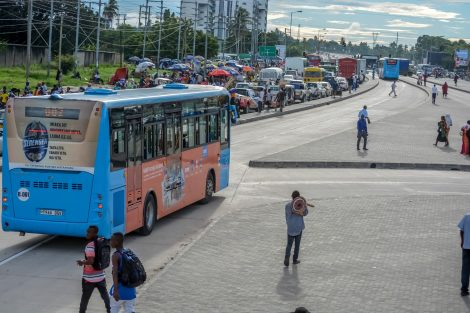 Blue DART bus passes on road in Dar es Salaam on a sunny day.
