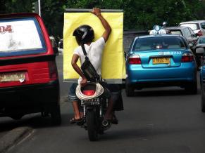 Motorcycles are used as taxis in Indonesia.