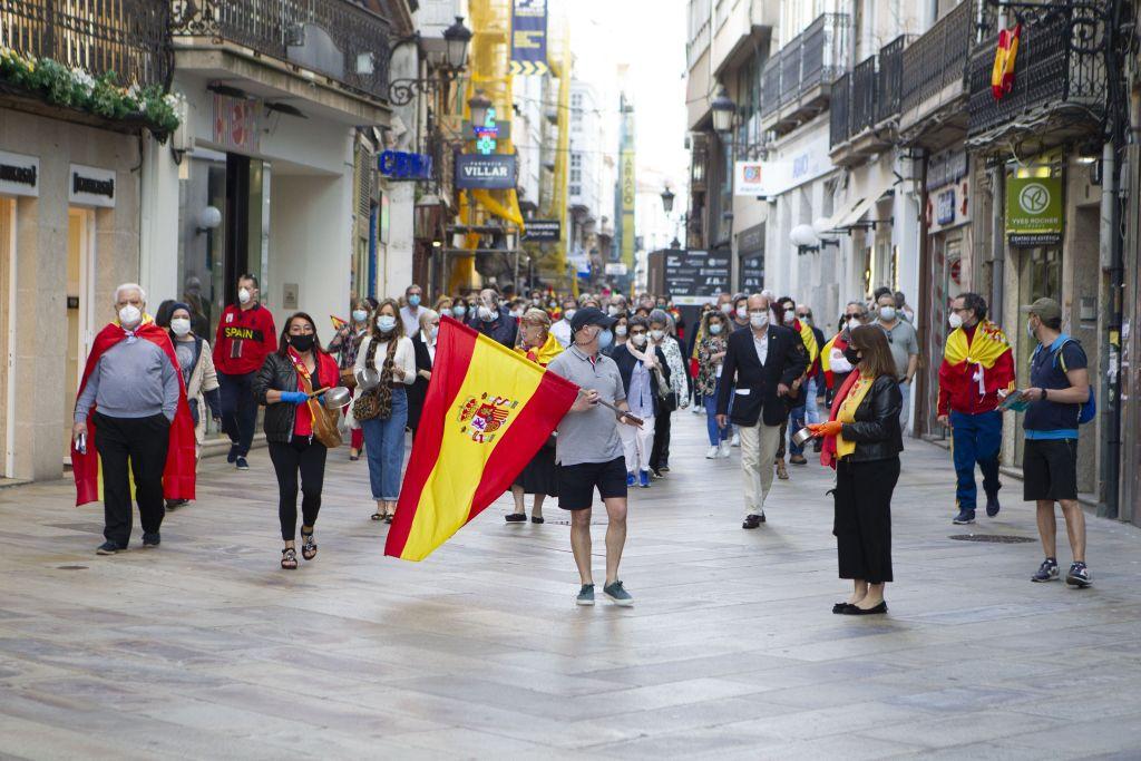 Manifestantes españoles con mascarilla protestan tocando una cacerola contra la gestión del gobierno español durante la pandemia del Covid-19 (Lago Loópez/Dreamstime)