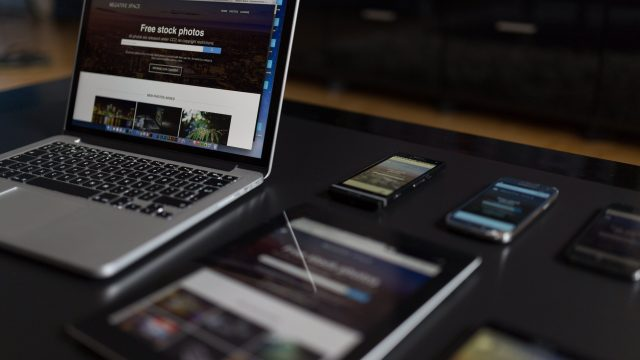 Diferentes dispositivos (celulares, tablets, notebooks) sobre un escritorio.