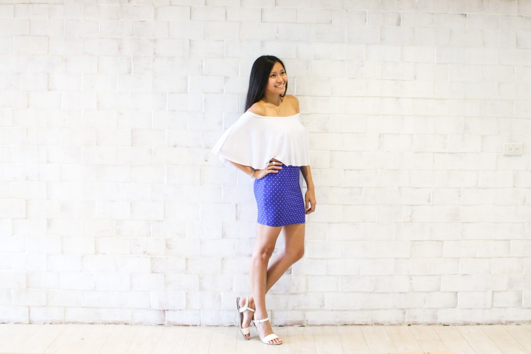 Adi Amor in a white off-shoulder top and blue polkadot skirt and white sandals
