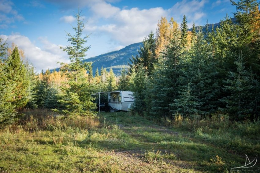 23ft travel trailer in British Columbia. Surrounded by trees and mountains.