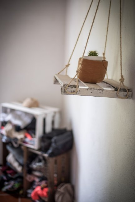 hanging planter with wood crate clothing storage