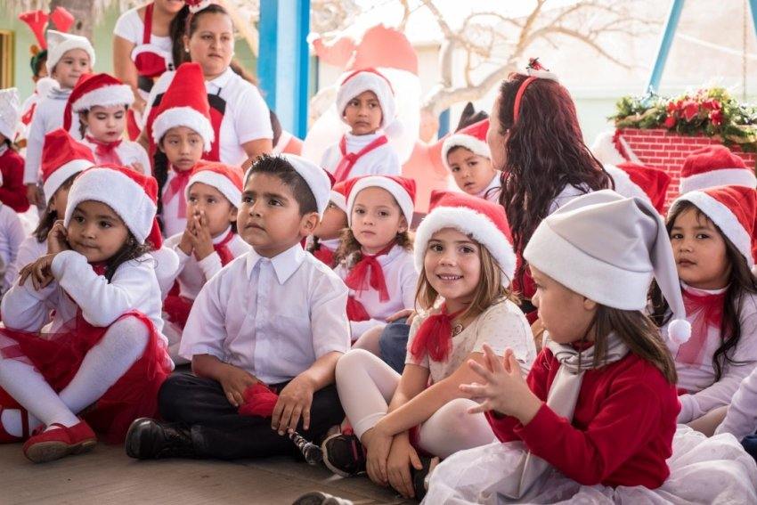 Ellia sitting with her class at a Christmas presentation
