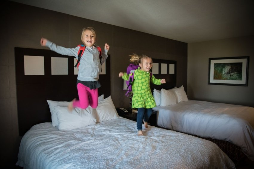 Kids jumping on hotel bed