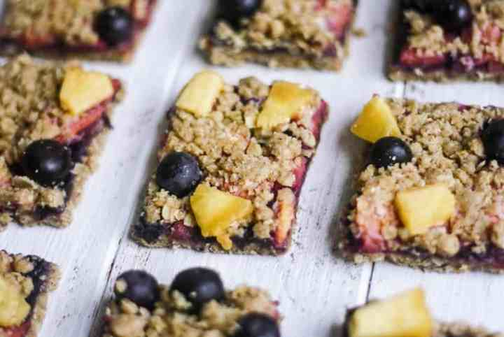 Soft and chewy oatmeal bars topped with fresh peaches, blueberries and a sweet crumble topping | It's Cheat Day Everyday