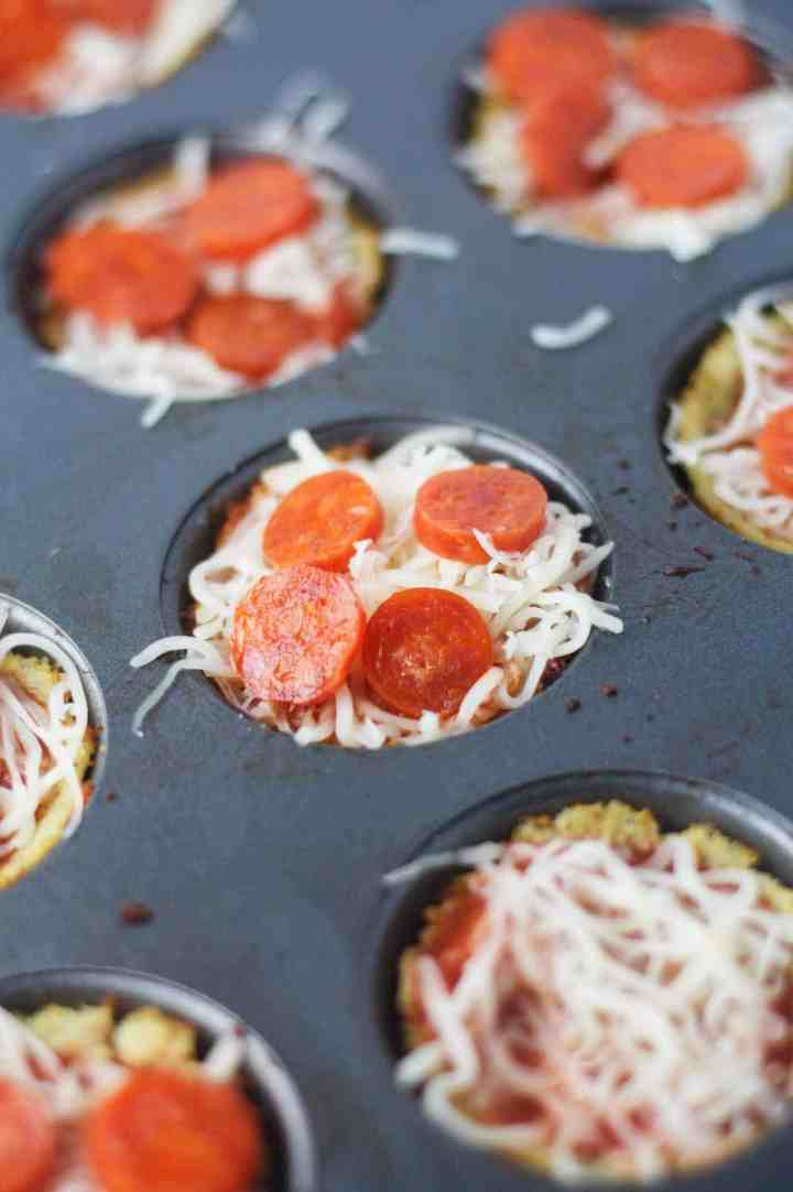 Mini low carb pepperoni pizzas made with a super easy, 3 ingredient cauliflower crust. A deliciously healthy, paleo friendly alternative to pizza rolls! www.itscheatdayeveryday.com