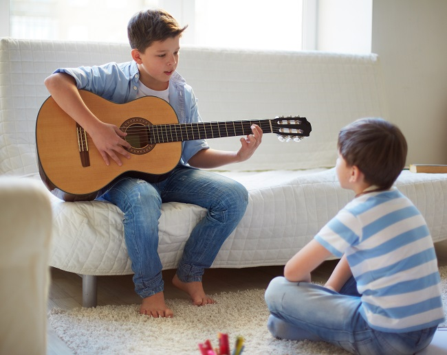 boy playing the guitar with his brother near by