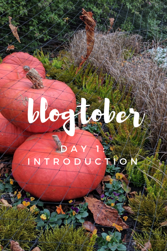 "the spicy bean - vertical pinterest image showing five pumpkins in a shrubbery, overlayed with the text ""blogtober day 1 - introduction"""