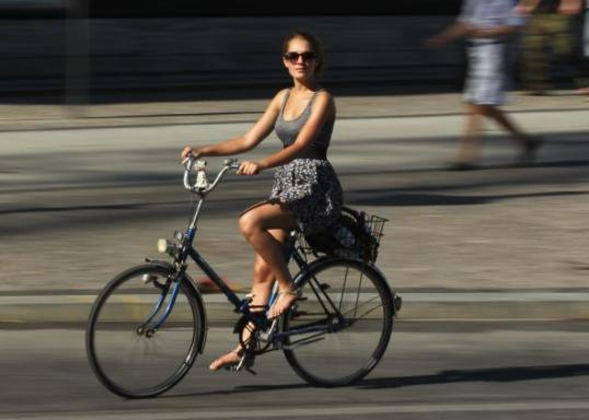 117638917-young-woman-rides-a-bicycle-on-a-hot-day-in-the-city.jpg.CROP.promo-mediumlarge