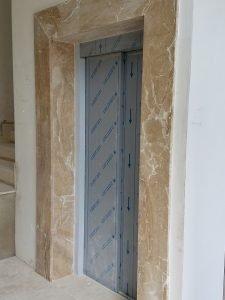 elevator's doors framed in marble