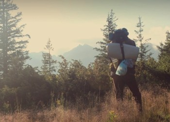 A woman hiking in woods, prepare for your hike with our free hiking essentials checklist.