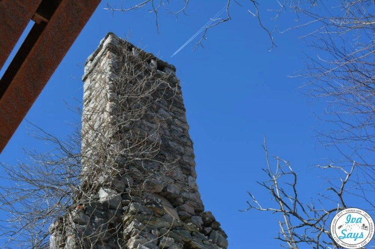 An airplane passing over the chimney that is part of the Van Slyke Castle.