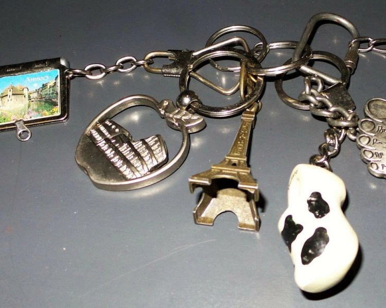 Different key-chain figures such as the Eiffel Tower, a boot from Holland, to represent different countries visited by purchasing these travel souvenirs.