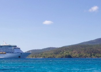 9 Important Questions To Ask Before Booking Up That Cruise: A White Cruise Ship in the water approaching land.