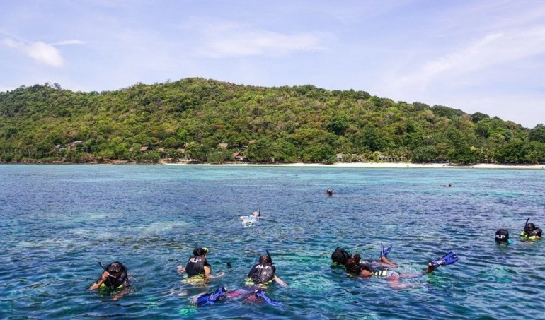 People snorkeling and diving in a body of water in Thailand, Asia.