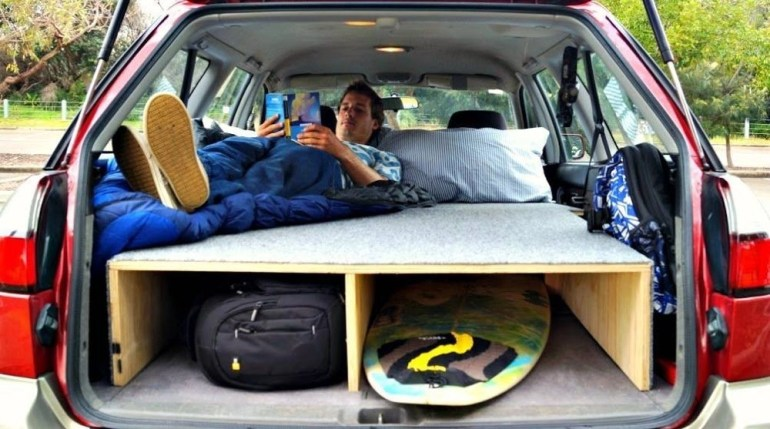 Turn your car into a hotel on wheels with few modifications - a man resting in the back of his car.