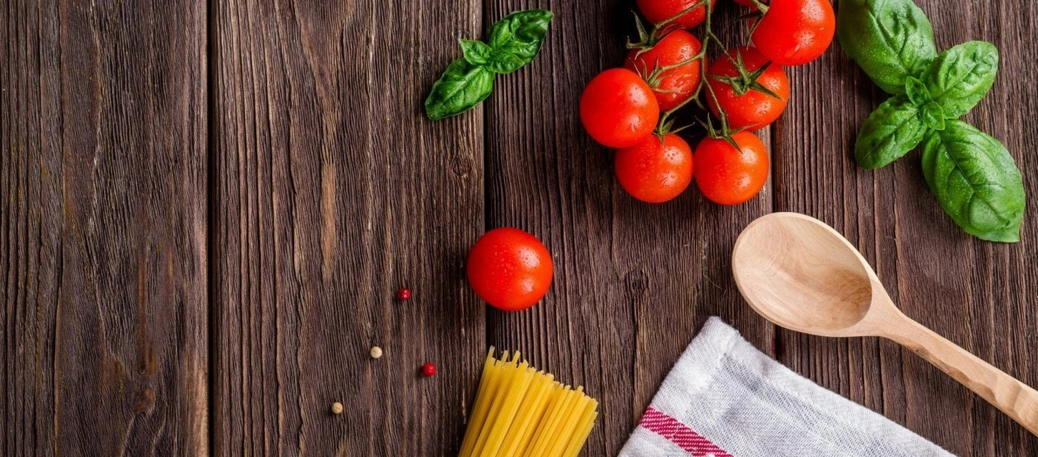 Bringing Food on Road Trips: tomatoes, basil, spaghetti, and a cooking cloth laid out on a wooden table.
