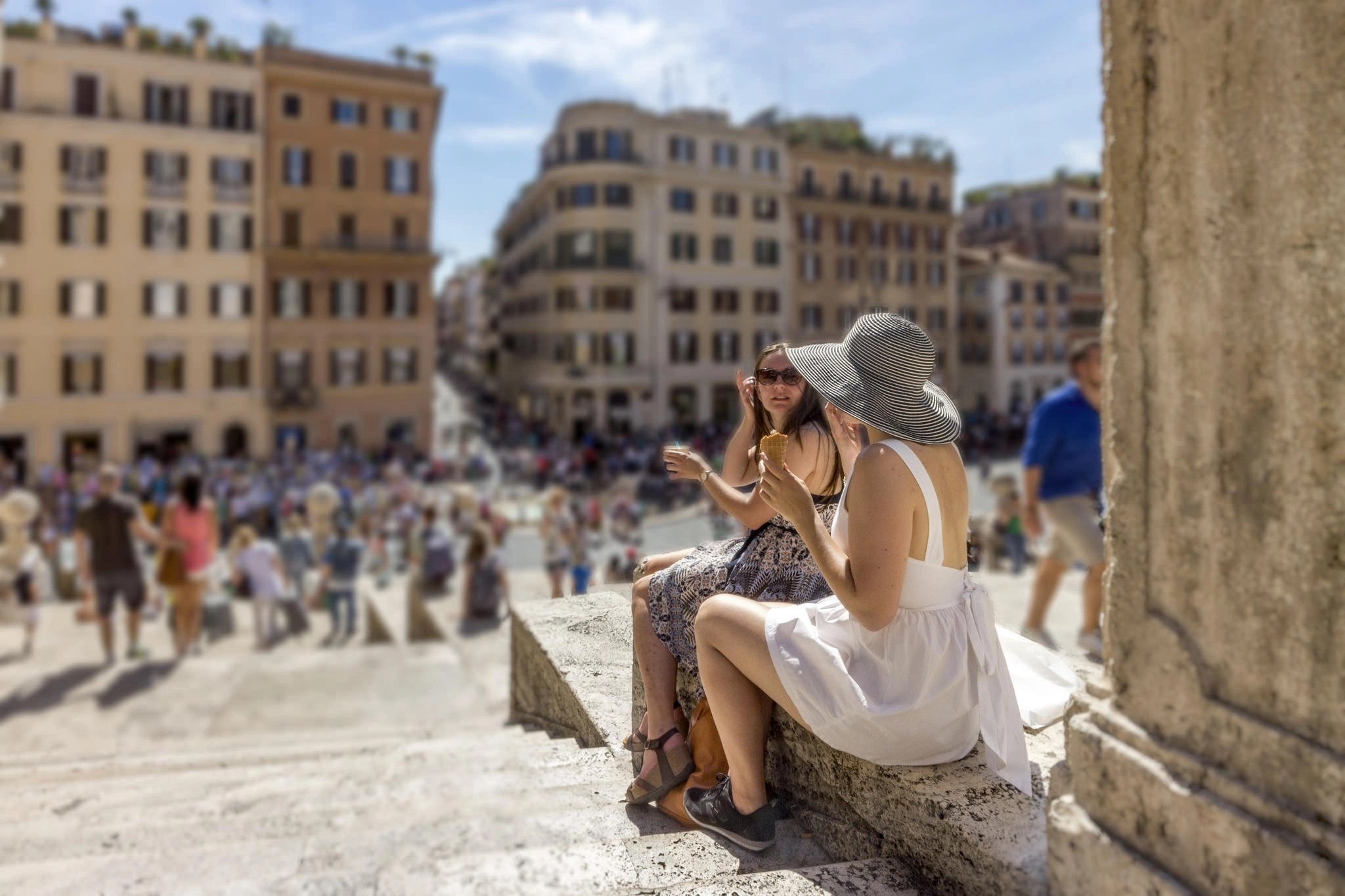 Two women sitting on the Spanish Steps in Spagna, Rome with buildings in the background and people walking in the plaza.