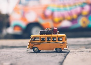 A yellow toy mini van from the 70s with luggage on the roof - going on a luxury vacation.