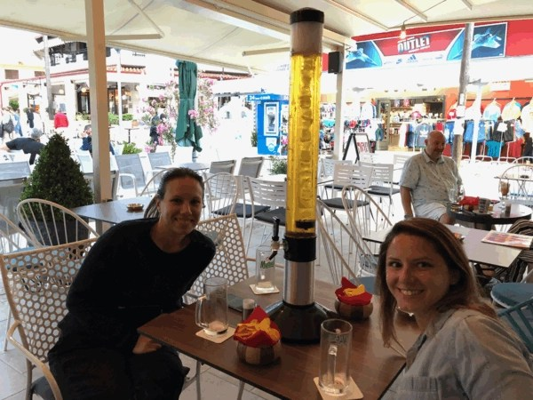 MIlena and Stephanie, my travel partners, posing at a local cafe in Chaniotis with a three liter tower of Mythos beer on the table,