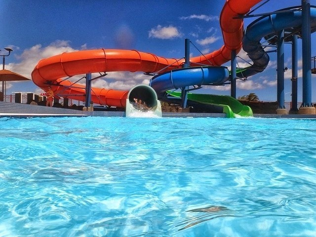 Kids coming out of a red water slide about to enter into a pool.