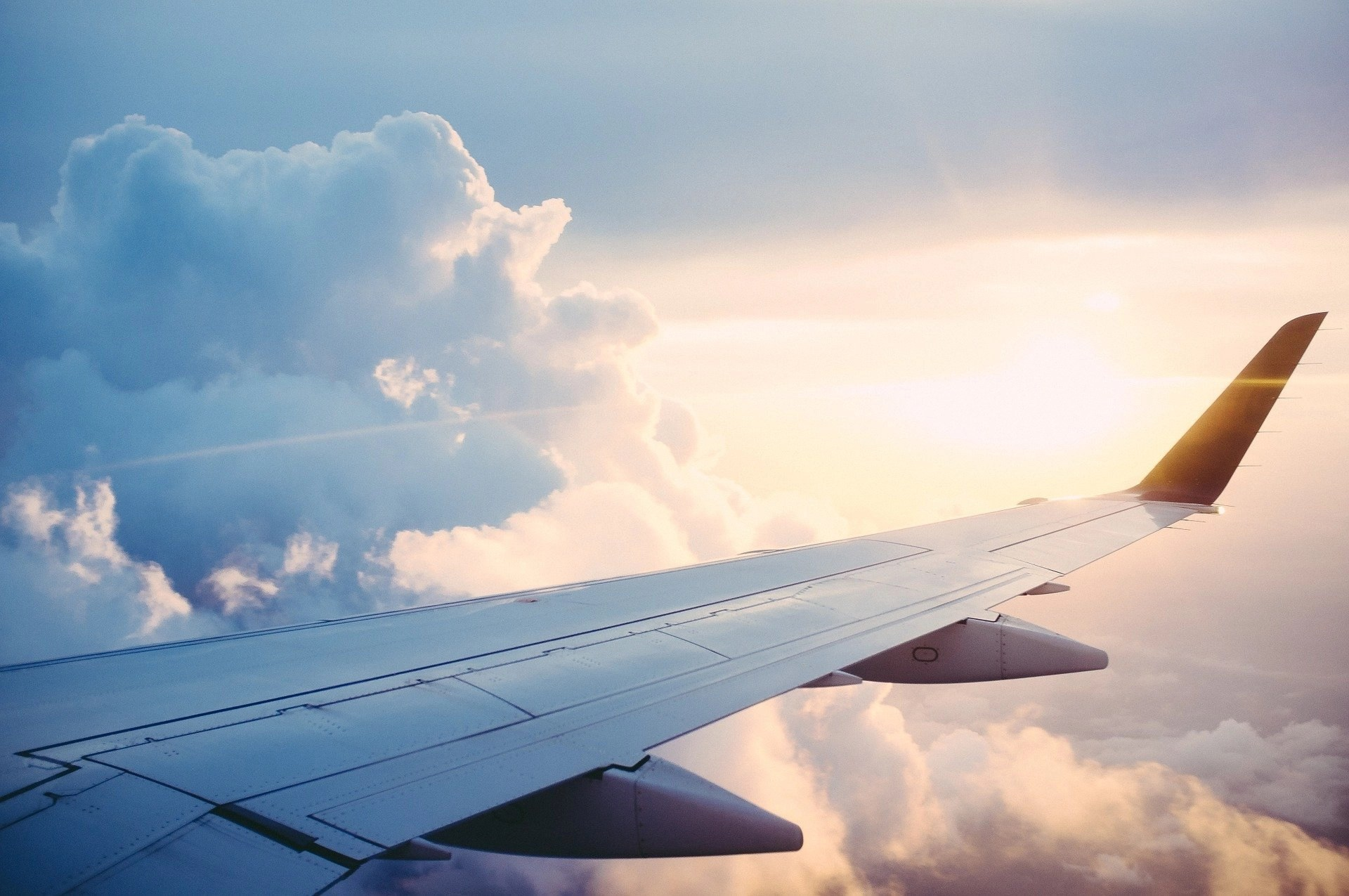 An airplane wing in the sky around clouds and the sun on the horizon. 3 Rules for Planning a Successful Trip Abroad. How to save money and return home after your trip abroad with a smile on your face.
