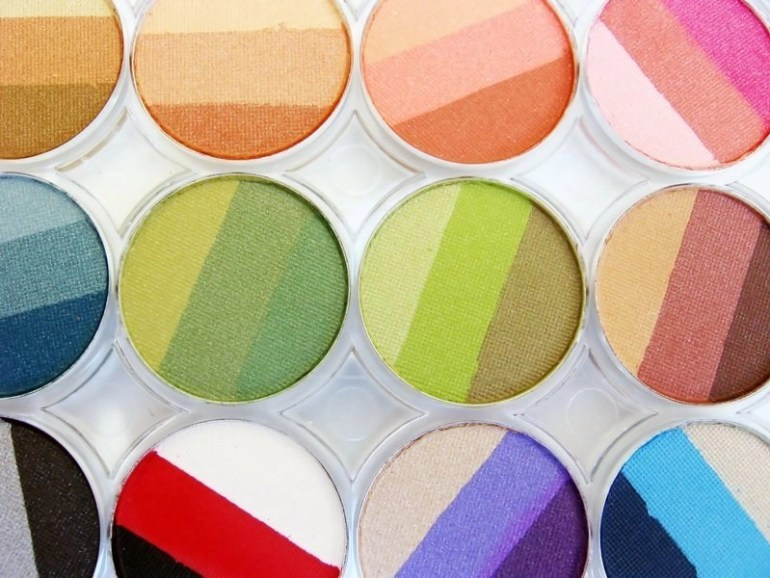 Multiple makeup or cosmetic metal containers with different eye-shadow colors that have three color varieties in each container.