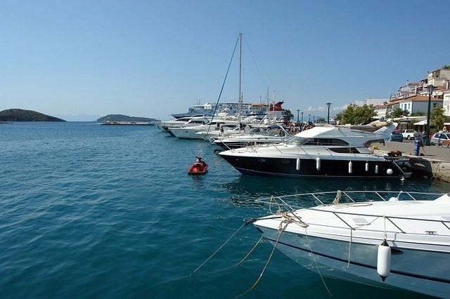 Multiple boats and yachts parked at a marina in open water body with a small red ski jet in front of the second yacht that is blue and white. Renting a boat is one option to experience your vacation in a luxurious way (luxury lifestyle travel tips).
