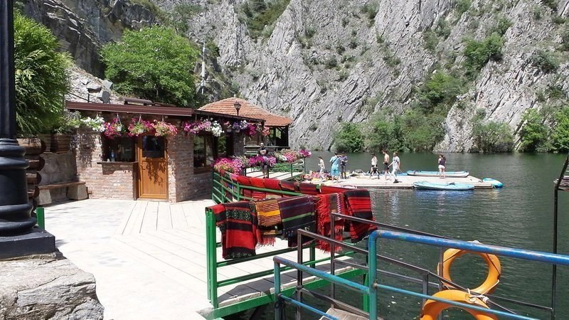 Traditional North Macedonian red and black rugs on a green railing at Lake Matka.