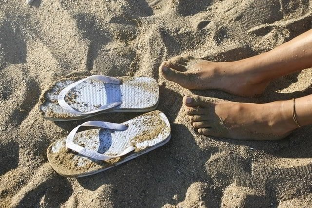 A pair of woman's feet in the sand on the beach with white flip-flops next to them.