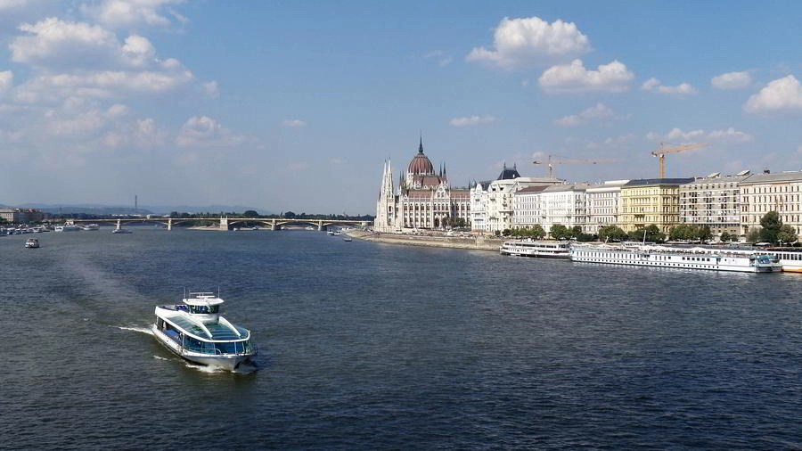 A tourist cruise boat on the Danube river by the Parliament river.