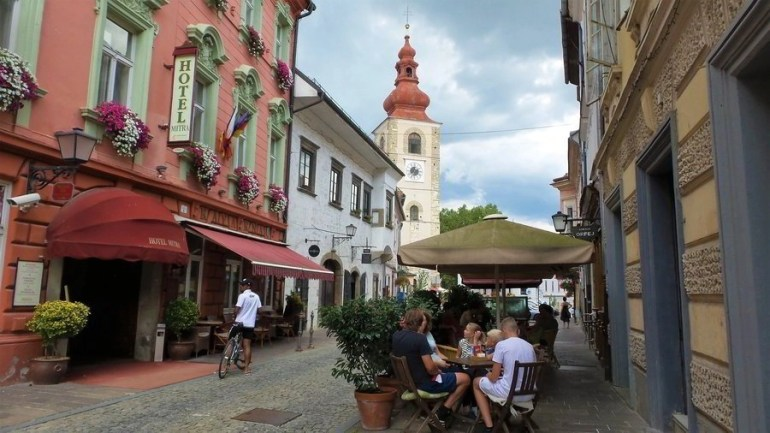 People sitting in a cafe by a hotel in the old town with the City Tower in the background.